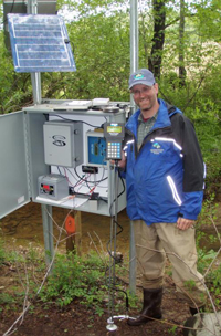 Photo of a man standing next to a stream gage.