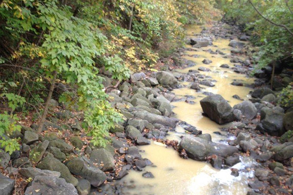 Stream with illegal dumping contamination