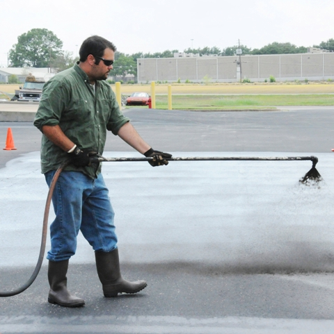 Image of a scientist spraying coal tar sealant during a test.