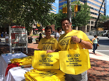 Two men holding yellow bags with Look Out For Each Other message.
