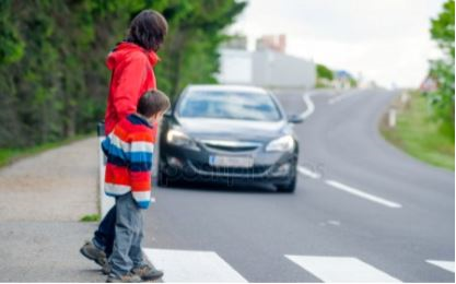 photo of a woman and child crossing the street with a car waiting