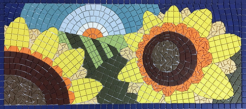 Mosaic of sunflowers against horizon with rising sun.