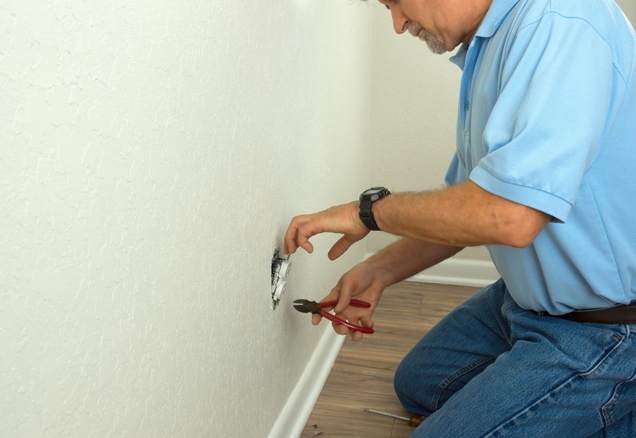 Homeowner installing electrical outlet in wall