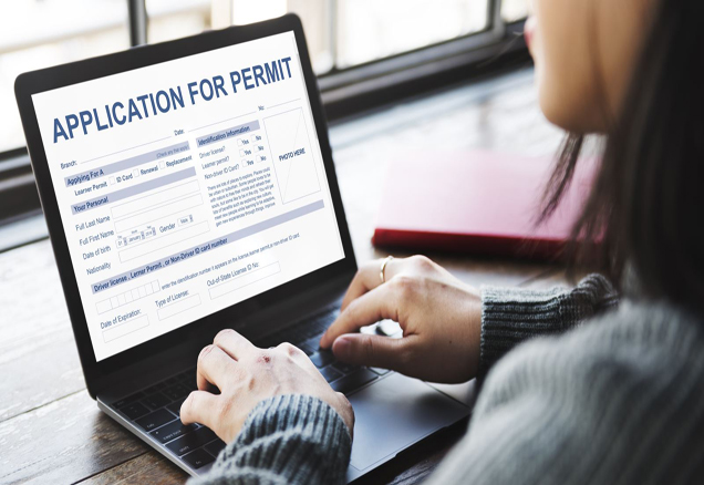 Woman with computer and Permit Application on screen