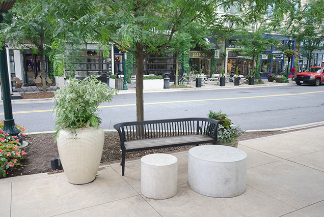 planters and a bench on a public sidewalk near a city street