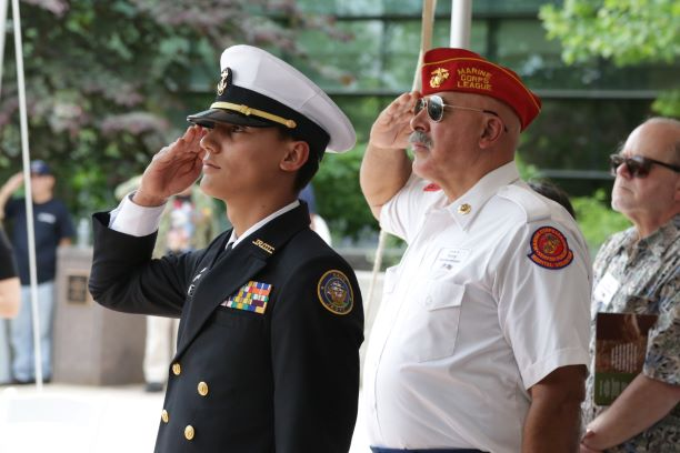 A member of ROTC and a Vietnam Veteran stand at attention during the singing of the national anthem