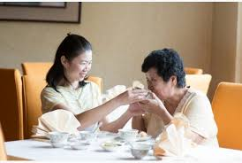 Asian woman feeding elderly mother