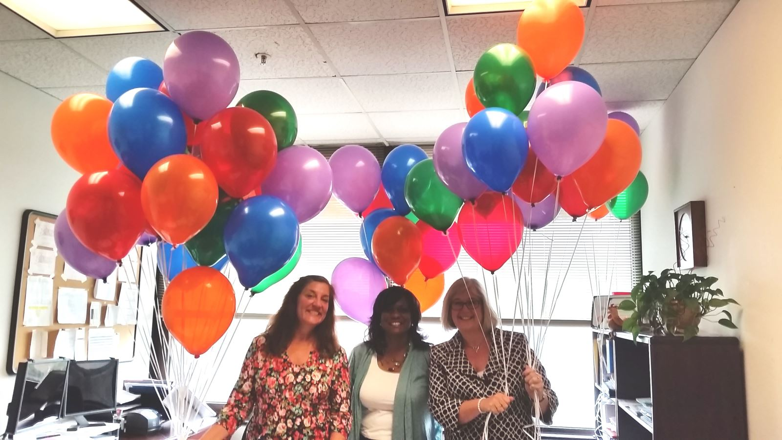 Three women holding balloons.