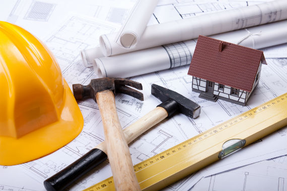 image of tools, miniature house, blue prints and yellow hard hat
