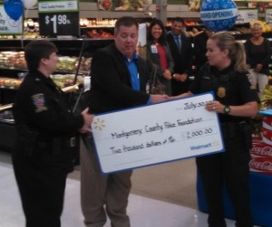 Assistant Chief Betsy Davis (left) and Officer Laurie Reyes (right) accept the check from Walmart