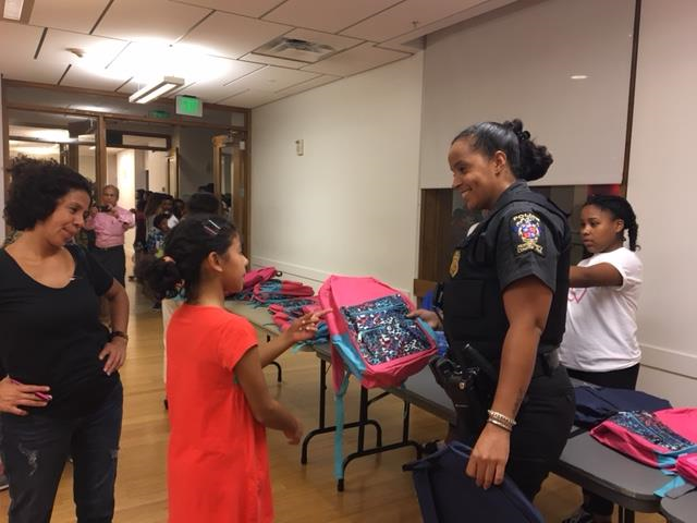 3rd District Community Services Officer Glenda Joseph handing out backpacks during the