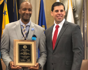 MCPD Detective John Witherspoon (holding award) with DOJ Acting Associate Attorney General Jesse Panuccio.