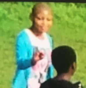 Photo out of focus but shows Natasha Mukuka (in blue sweater) with her hair shaved.