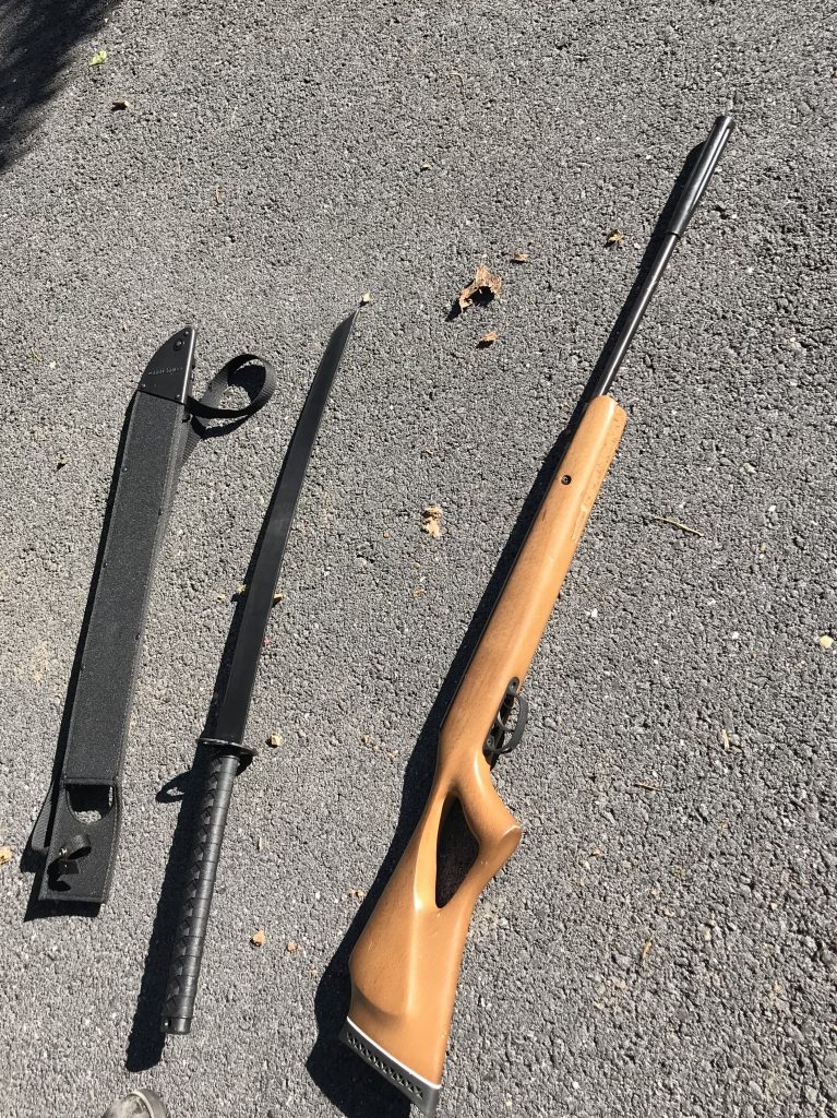 Weapons seized from home: three-foot sword with sheath (left), replica long gun (right)