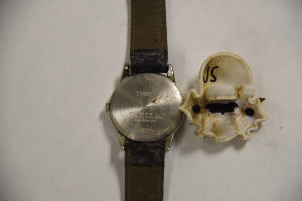 Photograph of back of watch and back of ring that was found with the decedent.