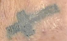 Tattoo Below Right Eye of a Cross
