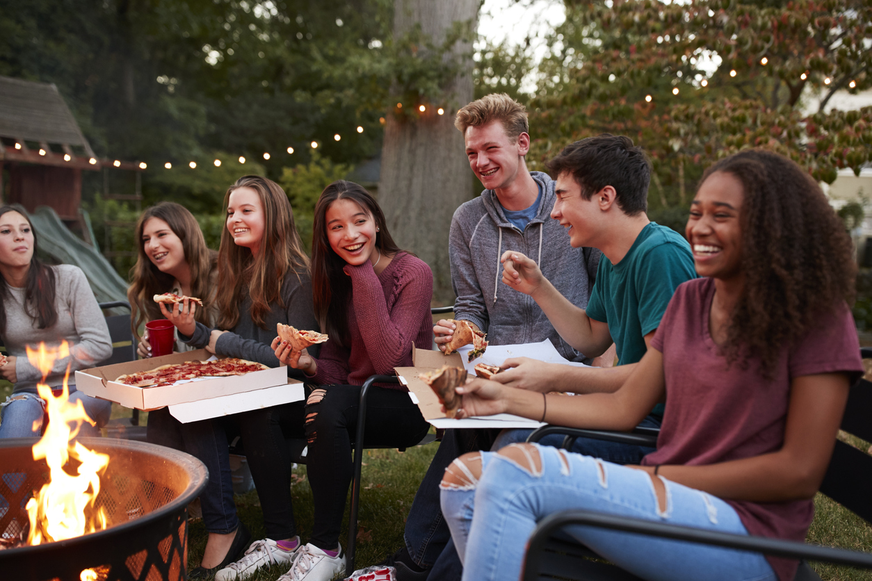 Group of Teens Hanging Outside Eating Pizza