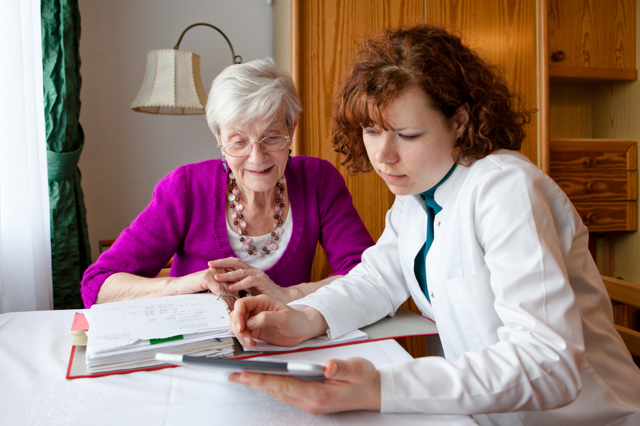 Younger woman helping older woman with paperwork