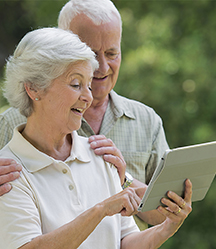An older couple looking at a tablet screen.