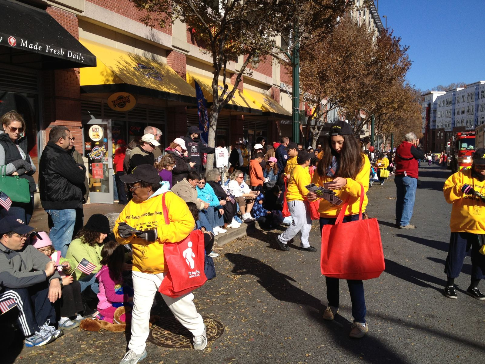 Photo of volunteers handing out reflective materials to the crowd at the 2012 Thanksgiving Parade