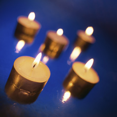 photo of several lit tea candles on a surface