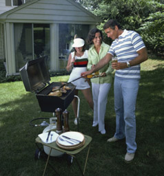 photo of man, woman and child by a BBQ grill