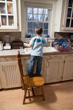young child home alone at kitchen sink