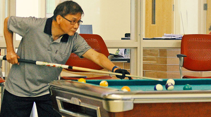 Man playing pool - Plum Gar Community Recreation Center